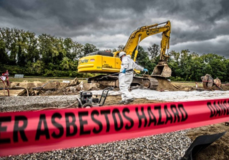 excavator and worker with a close-up of hazard tape