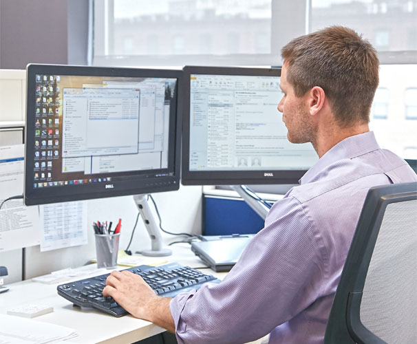 Man sitting at desk working on a computer for project engineer development program
