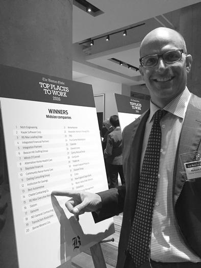 Bob pointing at charter on the list of globe's top places to work