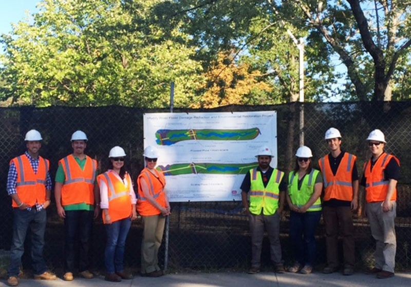 employees posing by a diagram of the muddy river